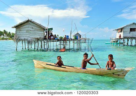Unidentified Bajau Laut kids paddling a boat