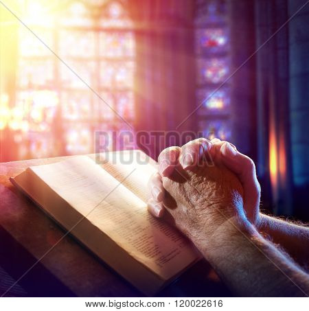 Hands Of A Man Praying With Bible