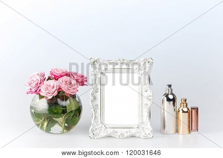Flowers vase and vintage frame on white