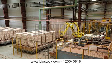 Laying bricks on pallets in manifacturing workshop