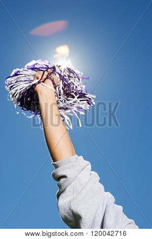 Arm of a cheerleader holding pom-pom