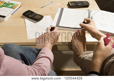 Two female students painting their toenails