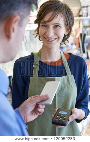 Man Using Contactless Payment App On Mobile Phone In Store