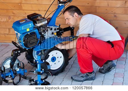 Small Scale Agriculture - Man Checking On Small Motorized Tiller Machine