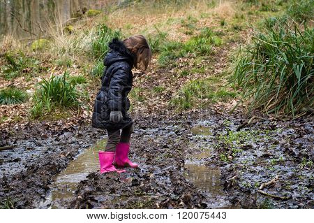 Child In Mud On Track Through Woodland