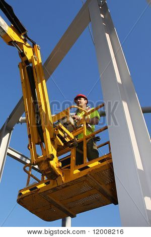 Steel worker operating cherry picker