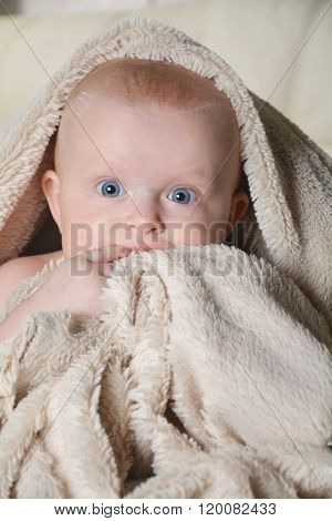 Baby With A Towel After The Shower In Bed At Home