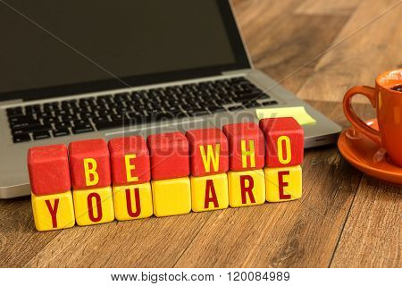 Be Who You Are written on a wooden cube in a office desk