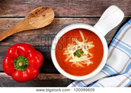 Red pepper soup overhead scene on rustic wood background