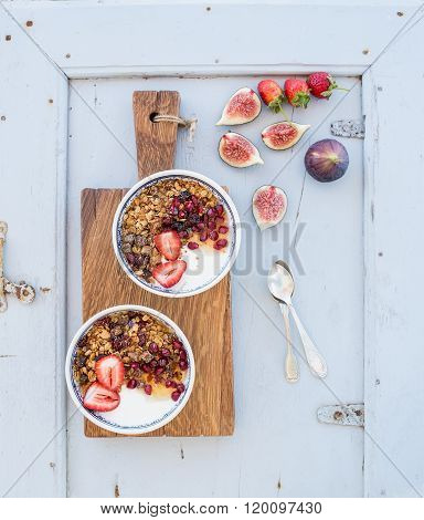 Healthy breakfast set. Bowls of oat granola with yogurt, fresh strawberries, figs, pomegranate andd