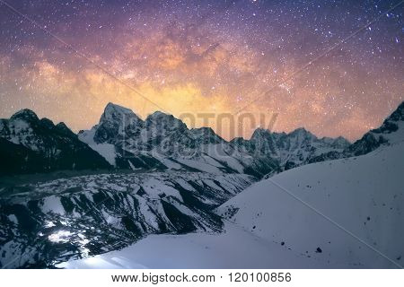 The Milky Way galaxy over the Himalayas. Nepal, Everest region, view of Chlolatse (6,440 m) and Taboche (6,495 m) peaks with Gokyo village (4,790 m) in front, captured from the Gokyo Peak (5,483 m).