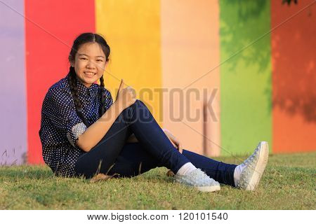 Asian Girl Relaxing Sitting On Green Grass Field Of Public Park And Hand Sign Ok ,all Right With Too
