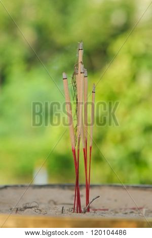 Burning incense sticks in Buddhist temple of Thailand.