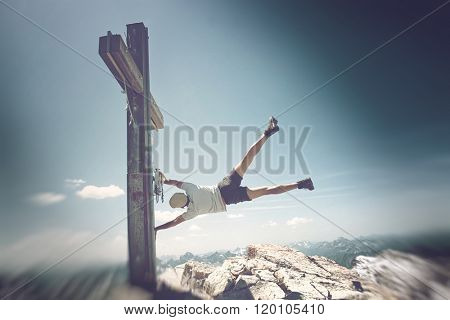 Humorous Image of Man Clinging to Summit Cross on Extremely Windy Day in Allgau Alps with View of Mountains in Background, on Sunny Day with Blue Sky