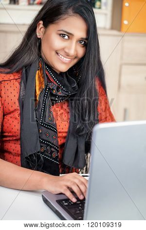 Young pretty india woman working at her laptop, vertical