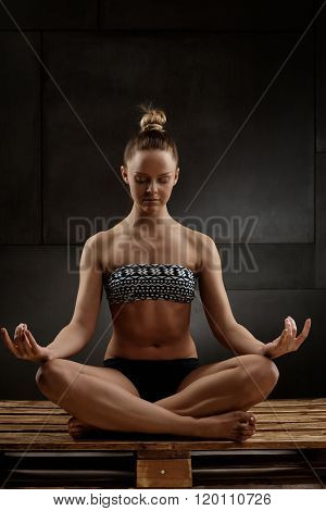 Young woman sitting in tailor seat, meditating in studio eyes closed.
