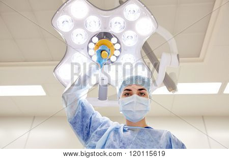 surgery, medicine and people concept - surgeon in mask adjusting lamp in operating room at hospital poster