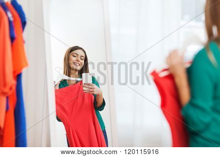 clothing, fashion, style, technology and people concept - happy woman with smartphone snd red dress taking mirror selfie at home wardrobe