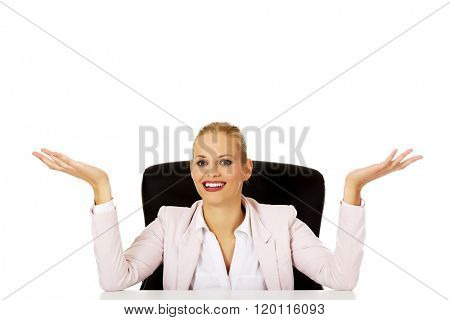 Business woman sitting behind the desk and making don't know sing