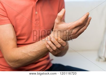 people, healthcare and problem concept - close up of man suffering from pain in hand oe wrist at home