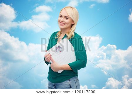 weight loss, diet, slimming, plus size and people concept - smiling young woman holding scales over blue sky and clouds background
