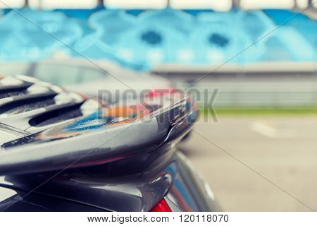 racing, motosports, extreme and motoring concept - close up of sports car back spoiler on speedway of stadium