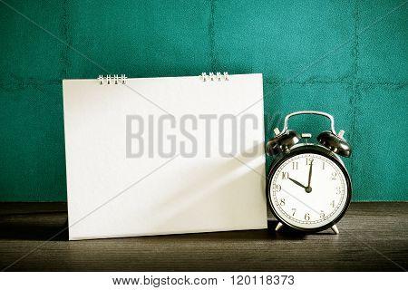 Stillife Of Desk Calendar With Alarm Clock On Wood Table. Vintage Filtered.