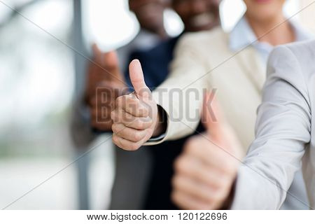 closeup of business people giving thumbs up