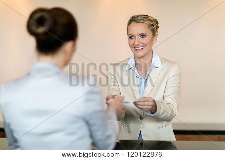 friendly hotel receptionist handing over key to customer