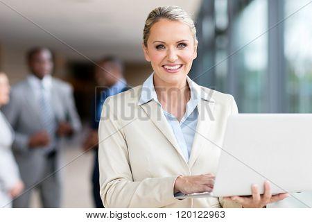 portrait of happy mature businesswoman using laptop computer