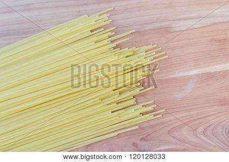 Uncooked pasta spaghetti macaroni on wood table