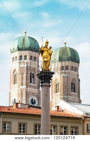 The Golden Mary's Column opposite the towers of the Cathedral of Our Dear Lady in Marienplatz in Munich, Germany, at daytime.