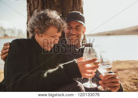 Relaxed Mature Couple Having A Glass Of Wine At Campsite