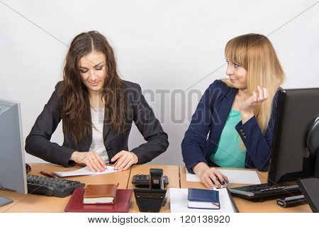 Two Young Girls Working In An Office, Making A Paper Airplane, And The Second With Hatred Looks At H