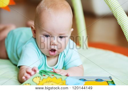Adorable baby looking a book