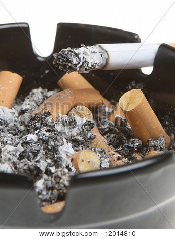 Close-up of lit cigarrette in a full ashtray.