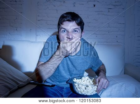 young attractive man at home lying on couch at living room watching tv eating crudely popcorn holding bowl looking mesmerized with blue eyes wide open in television addict concept