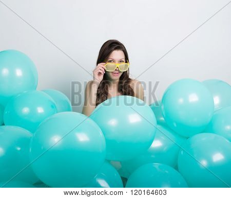 beautiful curly girl in a white dress and glasses in the style of disco playing with balloons.