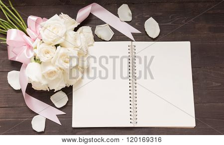 White Roses Flower With Ribbon Are On The Noteboo