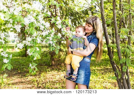 Happy woman and child in the blooming spring garden.Mothers day holiday concept