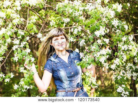 Beautiful spring woman in blooming tree