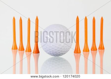 Golf Ball And Orange Tees On The Glass Table