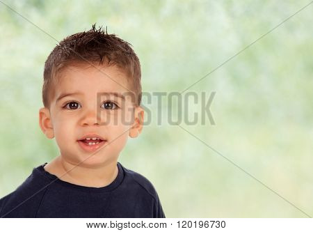 Adorable baby nine months looking at camera with green background