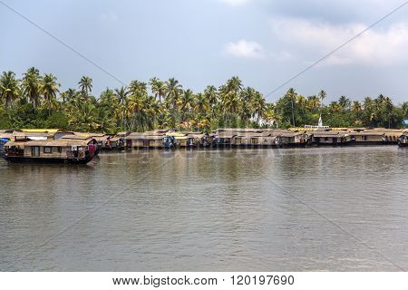 KERALA, INDIA - OCTOBER 16, 2015: Boats at backwaters in Kerala India. The backwaters are an extensive network of 41 west flowing interlocking rivers lakes and canals that center around Alleppey Kumarakom and Punnamada.