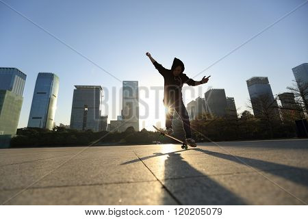 silhouette of skateboarder skateboarding at sunrise city