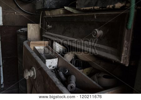 Open dusty old drawer full of tools in the workshop
