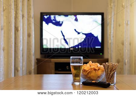 Tv, Television Watching (map Of Near East, News) With Snacks Lying On The Table