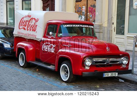 An old renovated red Ford vintage Coca cola truck (pickup) in a parking lot