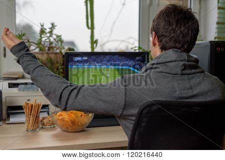 Male Gamer Playing Football Game On Computer With Snacks Lying On Table