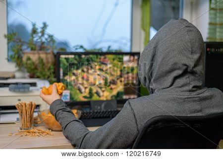 Male Gamer Playing Strategy Game On Computer With Snacks Lying On Table